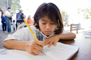 """A child studies at Fundaninas in Guatemala City, Guatemala. Fundaninas, which was founded by Rotarian Isabel de Bosch, houses, feeds, and educates abused and abandoned girls ages 2-18. It is supported by Rotary clubs in Guatemala City and Matching Grants from The Rotary Foundation. Now a Matching Grant project with the Rotary Club of Winterthur, Switzerland, is helping to provide a """"soy cow"""" - a machine that grinds and processes soy beans to make soy milk. Find the story in """"The Rotarian,"""" December 2010, pages 16-17."""
