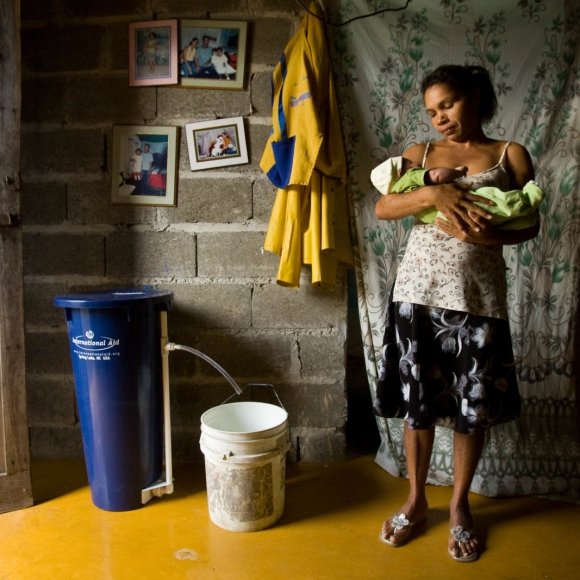 "Leonida Burges holds her infant son, Ricardo Daniel, while she filters water for the day in Aguas Negras, a neighborhood in Puerto Plata, Dominican Republic. She has had a bio-sand water filter in her home for two days. Find the story in ""The Rotarian,"" August 2009, pages 30-45."